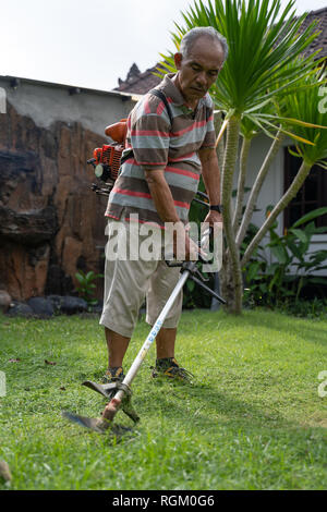senior asian man mowing grass at his own home garden  - Stock Photo