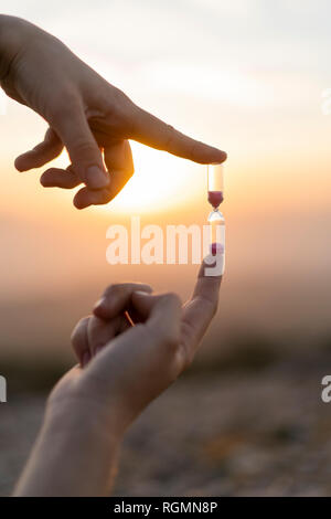 Close-up of man's hands holding an hourglass at sunset - Stock Photo