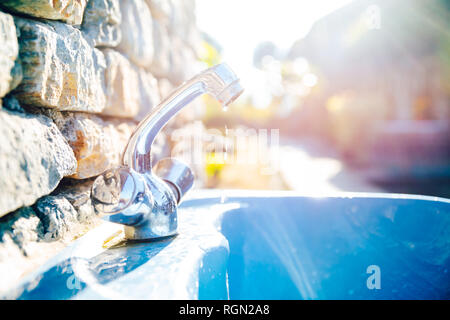 Outdoor washbasin in a garden, water dripping from tap. Waste concept. - Stock Photo