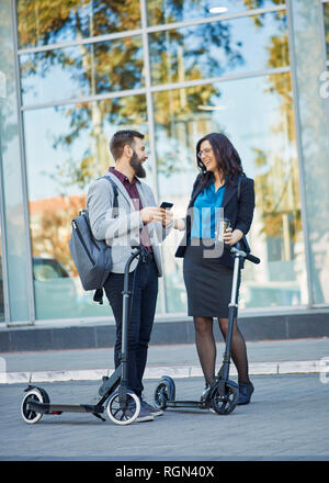 Happy businessman and businesswoman with scooters talking on pavement - Stock Photo