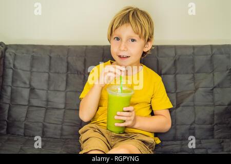 The boy is drinking Green tea latte with ice in mason jar. Homemade Iced Matcha Latte Tea with Milk zero waste - Stock Photo