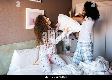 Young girl friends fighting with pillows in the bed - Stock Photo