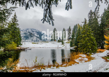 A small idyllic mountain lake near Montreux in Switzerland in early winter. - Stock Photo