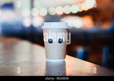 Coffee takeaway cup with cartoon eyes in cafe. Concept of hospitable cafe and good service. Cute and nice character. - Stock Photo