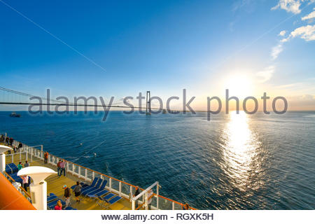 Tourists wait and take photos from upper deck as a cruise ship passes under the Oresund Bridge spanning the strait between Sweden and Denmark - Stock Photo