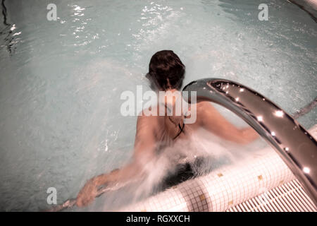 Woman Relaxing in a Hydro Massage Pool with Falling Water on Her Spine and Neck in Switzerland. - Stock Photo