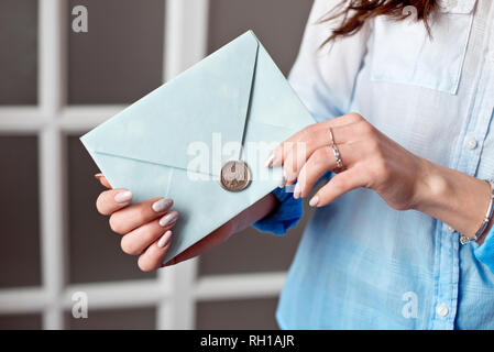 Close-up of a woman with a slim body holding a blue rectangular invitation card in an envelope of a card - Stock Photo