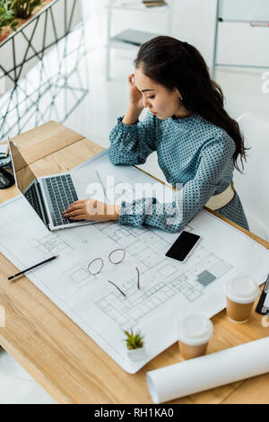 stressed asian female architect having headache while using laptop in office - Stock Photo