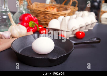 Fresh uncooked egg on a cast iron pan on the black background. - Stock Photo