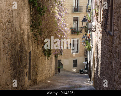 Steep Street down to a Cafe: Typical of the back streets in old Girona are the steep streets lined with old and some modern buldings - Stock Photo