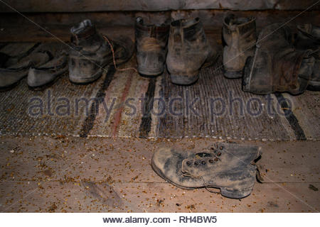 Closeup of old vintage shoes and leather boots in a wooden farm house attic. Selective focus on one leather boot in the front, blurred background. - Stock Photo