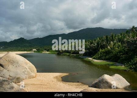 Coastal lagoon, smooth rocks, sand and tropical coastline vegetation at the scenic Arrecifes Beach. Tayrona National Park, Colombia. Sep 2018 - Stock Photo