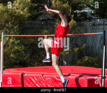 A high school track and field high jumper is taking off from the ground as he attempts to jump over the orange bar onto the red matts during a high ju - Stock Photo