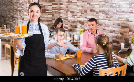 cheerful young waitress warmly welcoming guests to comfortable family cafe - Stock Photo