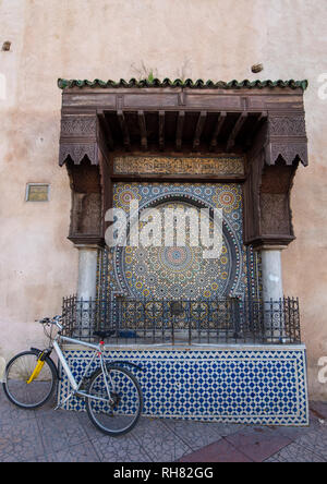 Traditional ornamental drinking fountain  in medina. Decorated fountain with mosaic tiles. Ornate mosaic and traditional Islamic religious art. Meknes - Stock Photo