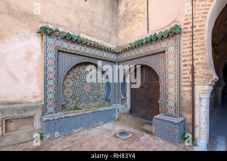 Traditional ornamental drinking fountain  in medina. Decorated fountain with mosaic tiles. Ornate mosaic in Meknes, Morocco - Stock Photo