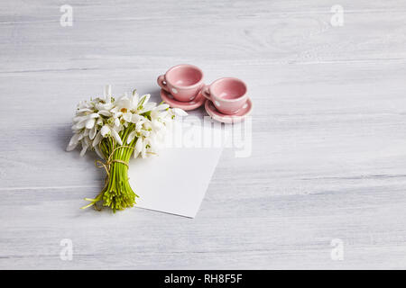 Two pink tiny dotted ceramic tea cups and a snowdrops bouquet on the white rusty wooden table. Place for text, blank piece of paper. Invitation card - Stock Photo