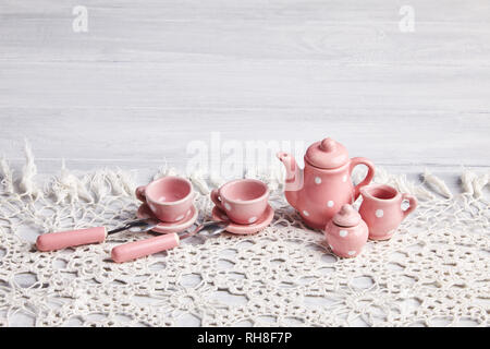 Pink tiny dotted ceramic utensils on the white rusty wooden table. Tea cups, a teapot, spoons and sugar bowl . Place for text. Invitation card - Stock Photo