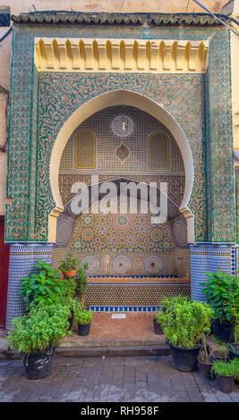 Traditional ornamental detail fountain in medina of Fez. Decorated fountain with mosaic tiles. Ornate mosaic and traditional art in Fes, Morocco - Stock Photo