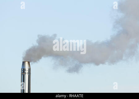 Air pollution from a biomass chimney flue pipe emitting smoke - Stock Photo