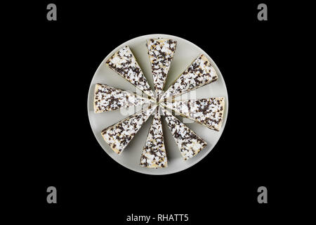 Cheesecake with chocolate chips on a white dish, isolated on the black background. Top view. - Stock Photo