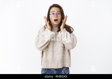 Worried and shocked cute woman showing empathy and shook as reacting to amazing terrible news open mouth and raising eyebrows with eyes in surprise - Stock Photo