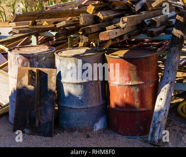 Rusty barrel oil on a partly black coloured beach illustrates the pollution of environment by oil spills rust - Stock Photo