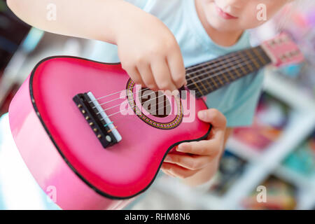 Little cute blond girl having fun learning to play small ukulele guitar at home.Toddler girl playing toy musical instrument indoors - Stock Photo