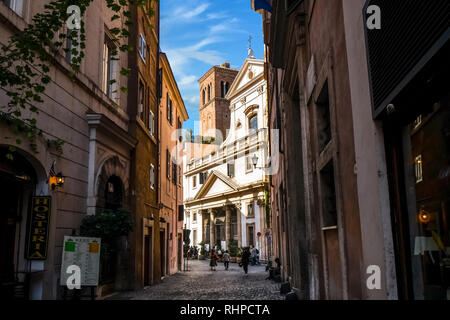 Tourists walk past shops down a shaded back alley towards the Saint Eustace Church with the White Stag sculpture on it's roof in Rome, Italy - Stock Photo