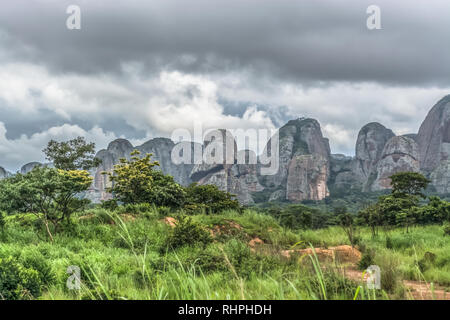 View of a tropical landscape, with forest and mountains Pungo Andongo, Pedras Negras , black stones, huge geologic rock elements, cloudy sky as backgr - Stock Photo