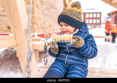 Little boy child 2-6 years old, eating corn in city in the winter in the fresh air in a blue overalls hat and mittens. Riding on a wooden swing. Free - Stock Photo