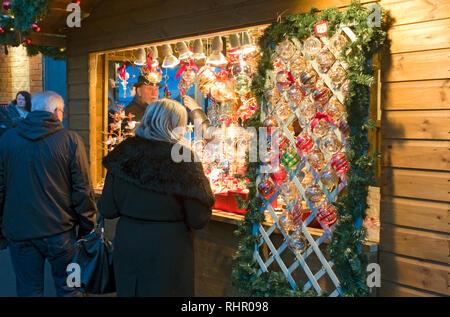Christmas cabin selling decorations at St Nicholas Fayre York North Yorkshire England UK United Kingdom GB Great Britain - Stock Photo