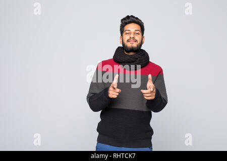 Young handsome indian man wearing casual sweater doing happy pointed on you gesture with hand on gray background - Stock Photo
