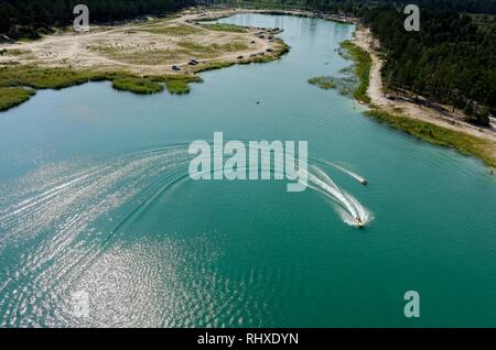 Aerial view onto beach on so-calles Blue Lake and hydrocycle tows the inflatable watercraft circle. Tyumen. Russia - Stock Photo