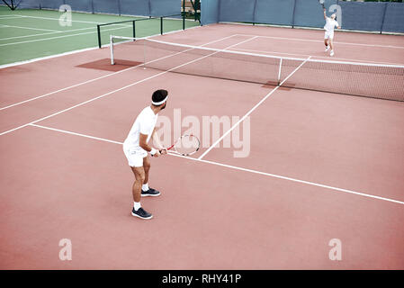 Tennis training. Tennis players practicing to hold serve on the court - Stock Photo