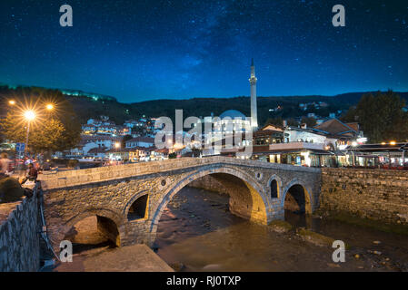 Night view of old stone bridge and old Ottoman Sinan Pasha Mosque in Prizren, Kosovo. Historic city, night landscape with star sky after sunset - Stock Photo
