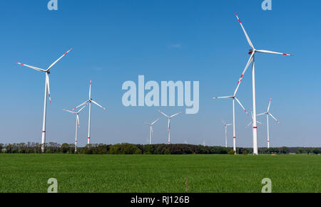 Wind power plants, green fields and blue skies seen in rural Germany - Stock Photo