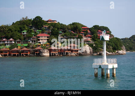 White port tower near Ko Pha-ngan island harbor in front of cliff cape with bungalow houses - Stock Photo