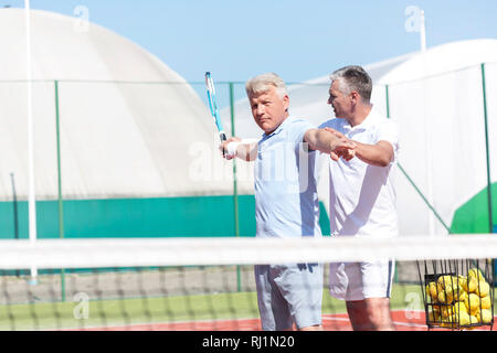 Mature man instructing friend swinging tennis racket on sunny day - Stock Photo
