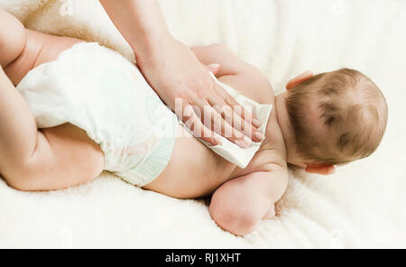 A newborn baby gets a diaper change: the mother wipes the baby with a baby wipe. The concept of cleanliness and care - Stock Photo