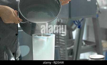 Worker pouring milk into container. - Stock Photo