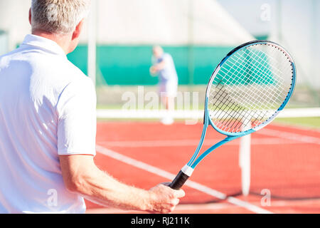 Rear view of mature man holding racket while playing with friend on tennis court - Stock Photo