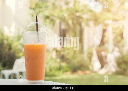 Iced tea with green tube in plastic glass. Natural garden background. - Stock Photo