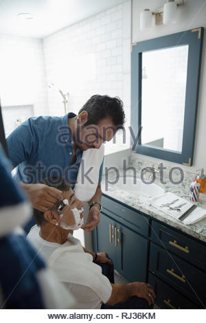 Latinx son shaving senior father s face in bathroom - Stock Photo