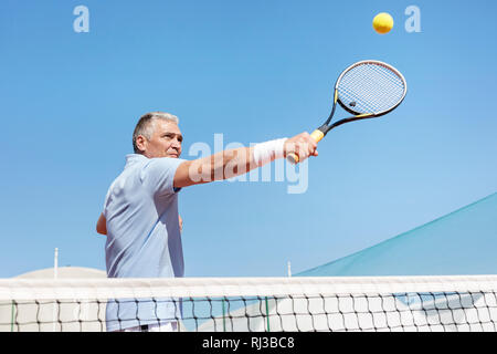 Low angle view of confident mature man hitting tennis ball with racket on court against clear blue sky - Stock Photo