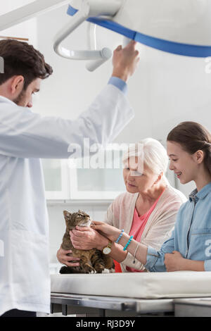 Doctor standing with woman and girl looking at cat in veterinary clinic - Stock Photo