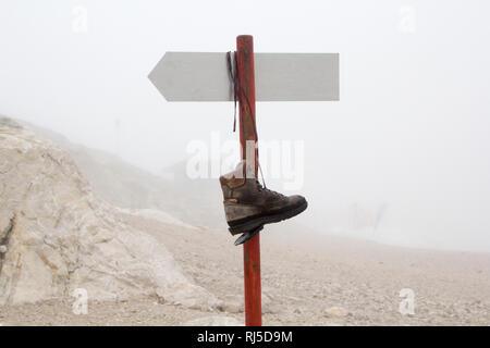 Ein kaputter Bergschuh hängt auf einem Berg an einem Wegweiser im Nebel - Stock Photo