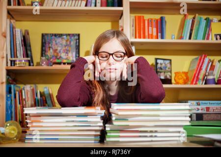 Mädchen, 10 Jahre alt, ermüdet von den Hausaufgaben, vor einem Stapel Bücher, mit geschlossenen Augen - Stock Photo