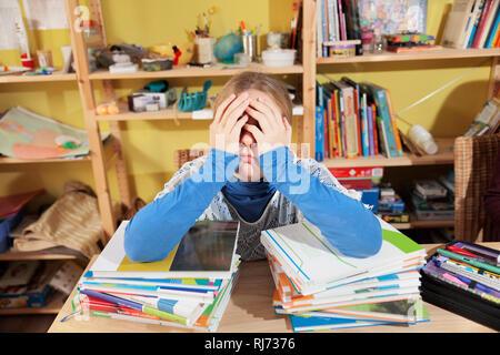 Mädchen, 10 Jahre alt, bei den Hausaufgaben, vor einem Stapel Bücher, überfordert - Stock Photo