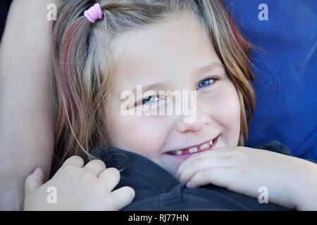 Portrait eines achtjähriges Mädchen in den Armen ihrer Mutter - Stock Photo